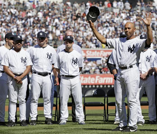 New York Yankees relief pitcher Mariano Rivera, right, acknowledges the crowd as he is honored in a pregame ceremony at Yankee Stadium before a baseball game against the San Francisco Giants, Sunday, Sept. 22, 2013, in New York. The 13-time All-Star closer is retiring at the end of this season. (AP Photo/Kathy Willens)