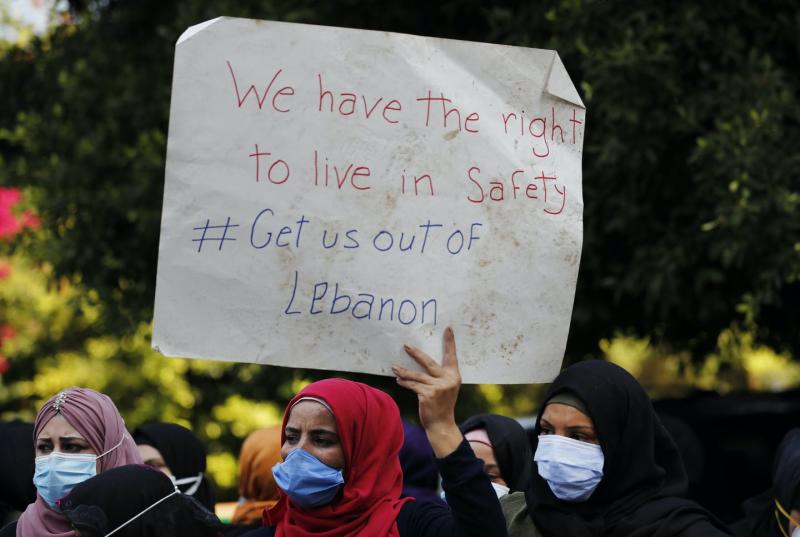 Women hold up a protest sign reading 'We have the right to live in safety. Get us out of Lebanon.'