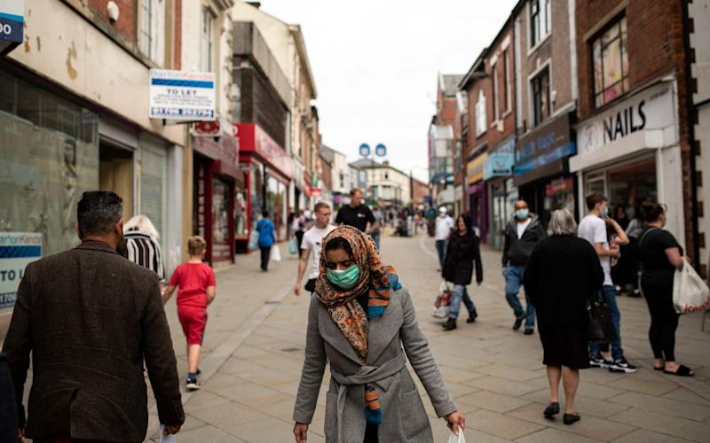 Pedestrians wear face masks as they walk down a street in Oldham, where virus cases are rising - Oli Scarff/AFP