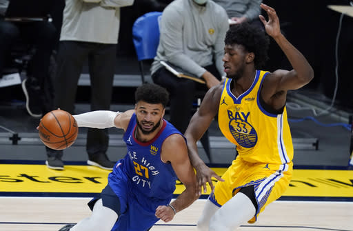 Denver Nuggets guard Jamal Murray, left, drives past Golden State Warriors center James Wiseman in the first half of an NBA basketball game Thursday, Jan. 14, 2021, in Denver. (AP Photo/David Zalubowski)