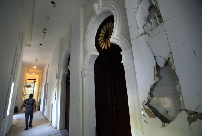 A worker walks in a corridor of the Sursock Museum that is still under reconstruction a year after being damaged in the massive explosion at the nearby port, in Beirut, Lebanon, July 27, 2021. The explosion ripped through the three-story building, unhinging the doors, wrecking everything down to the fourth underground level. The art collection was badly hit. (AP Photo/Hussein Malla)