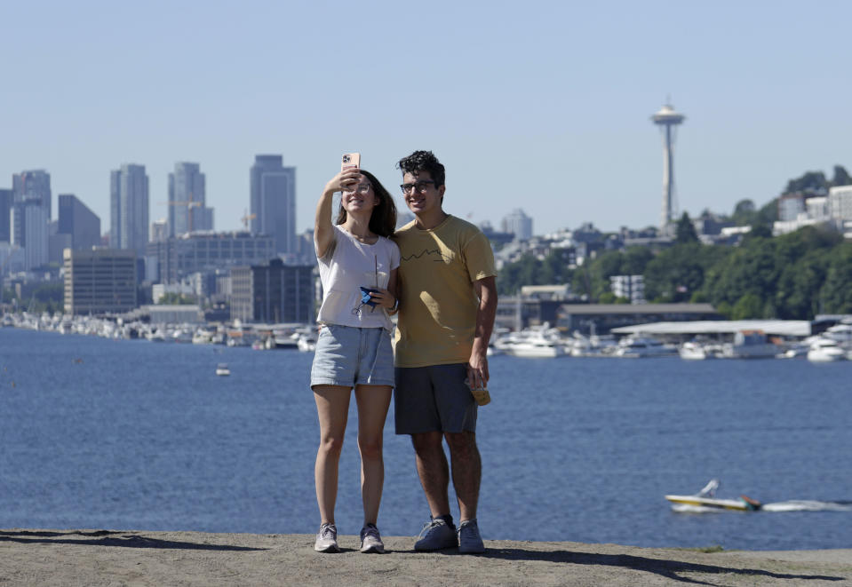 Zach Kamran and Anna Denson take selfies from the top of a hill at Gas Works Park in the morning during a heat wave hitting the Pacific Northwest, Sunday, June 27, 2021, in Seattle. Yesterday set a record high for the day with more record highs expected today and Monday. Kamran said they will likely spend the rest of the day inside as the heat rises. (AP Photo/John Froschauer)