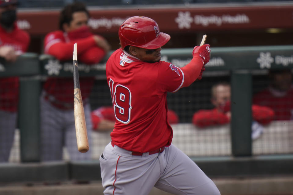 Los Angeles Angels' Juan Lagares breaks his bat as he hits a single in the second inning of a spring baseball game against the San Francisco Giants in Scottsdale, Ariz., Sunday, Feb. 28, 2021. (AP Photo/Jae C. Hong)