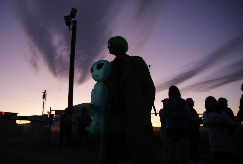 "Chase Hansen holds an inflatable alien near an entrance to the Nevada Test and Training Range near Area 51, Sept. 20, 2019, near Rachel, Nev. People came to visit the gate inspired by the ""Storm Area 51"" internet hoax. (Photo: John Locher/AP)"