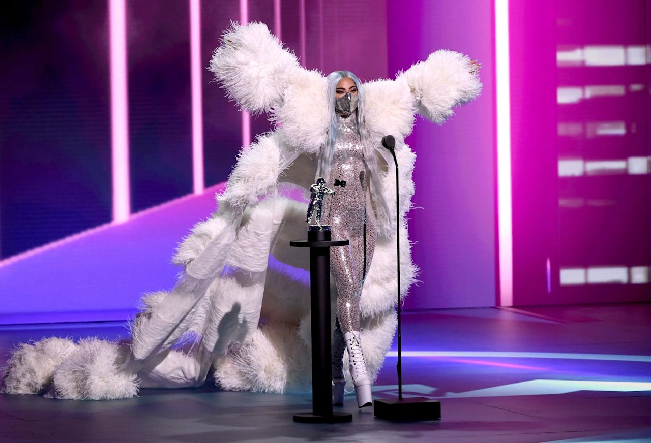 <p>Gaga wore a a dramatic feather coat and sequin catsuit from Maison Valentino to match her glittery mask.</p>