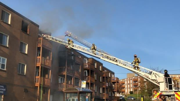 Firefighters are shown battling the fire at an apartment building on Primrose Street in Dartmouth, N.S., on May 19, 2018. (Emma Davie/CBC - image credit)