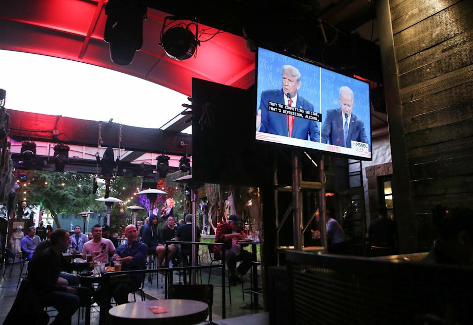 A patio TV shows the debate at a restaurant