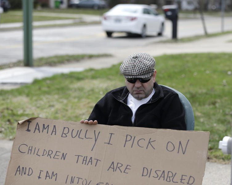 "Edmond Aviv sits on a street corner holding a sign Sunday, April 13, 2014, in South Euclid, Ohio declaring he's a bully, a requirement of his sentence because he was accused of harassing a neighbor and her disabled children for the past 15 years. Municipal Court Judge Gayle Williams-Byers ordered Aviv, 62, to display the sign for five hours Sunday. It says: ""I AM A BULLY! I pick on children that are disabled, and I am intolerant of those that are different from myself. My actions do not reflect an appreciation for the diverse South Euclid community that I live in."" (AP Photo/Tony Dejak)"