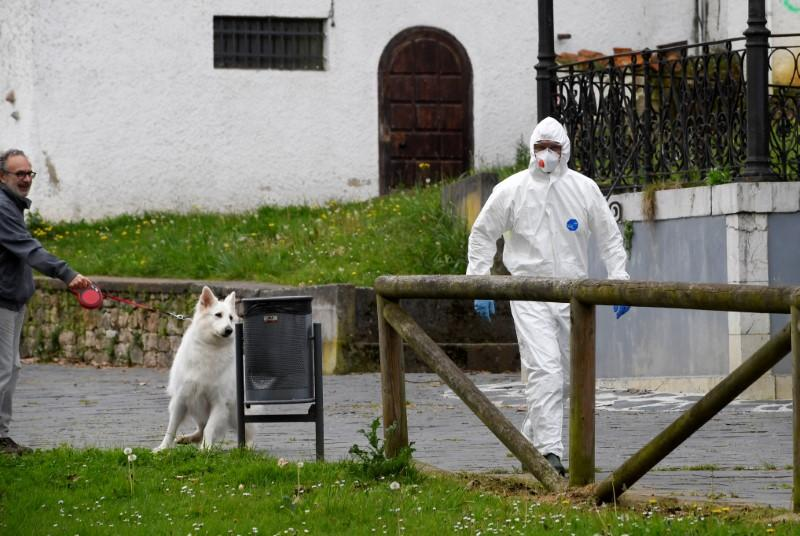 A sanitary worker walks past a man with a dog near the nursing home where a woman died and several residents and care providers have been diagnosed with coronavirus disease (COVID-19) in Grado