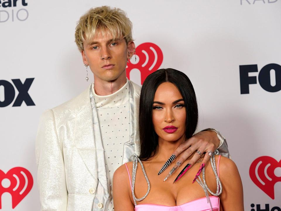 Machine Gun Kelly with his left arm around Megan Fox's shoulder at the red carpet of the 2021 iHeartRadio Music Awards.