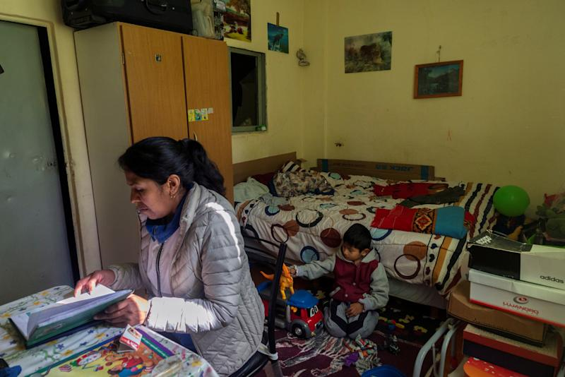 "Brigida Simaniz checks the homework of her son Nicolas, 7, in her apartment in the shantytown of Bajo Flores in Buenos Aires, Argentina Aug. 19, 2019. Brigida Simaniz finished her TB treatment earlier this year in May. She works in a textile workshop on 70 pesos ($1.19) an hour and lives with her two children, all three sharing the same bed. Her fear was passing the infection to her kids. ""I was scared when they told me the diagnosis because I did not know it existed. I always followed the treatment as the doctors said for fear of infecting my children,"" said Simaniz. ""Even though it was cold at night, I opened the windows of the room to circulate the air."" Cases of the ""white death"" illness, closely linked to poverty, malnutrition and poor housing, have been on the rise since the turn of the decade as Latin America's third largest economy has grappled with repeat recessions and inflation. (Photo: Magali Druscovich/Reuters)"