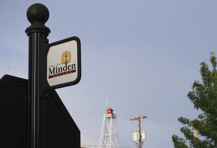 """This June 30, 2021 photo shows a sign for the town of Minden, Nev. Efforts to silence the century-old siren, seen in the background, that blares every night at 6 p.m. are sparking debates over how to confront the region's history of racism and violence. The Washoe Tribe of Nevada and California associates the siren with a historic """"sundown ordinance"""" that once made it illegal for them to be in Minden and neighboring Gardnerville after nightfall. Residents of the mostly white town defend it as a tradition that marks time and honors first responders. After state lawmakers banned the siren, the Washoe Tribe's chairman and Minden town manager agreed to move the siren to 5 p.m. but the compromise left many tribal members unsatisfied and awaits discussion at the tribal council. (AP Photo/Sam Metz)"""