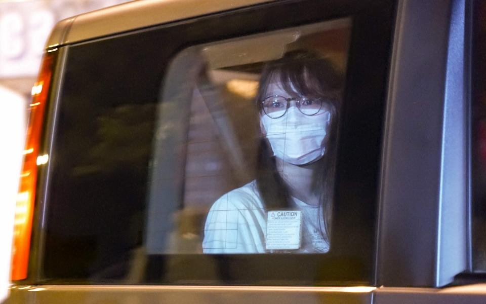Prominent Hong Kong democracy activist Agnes Chow looks out of a car window while being driven away by police from her home after she was arrested under the new national security law in Hong Kong - AFP