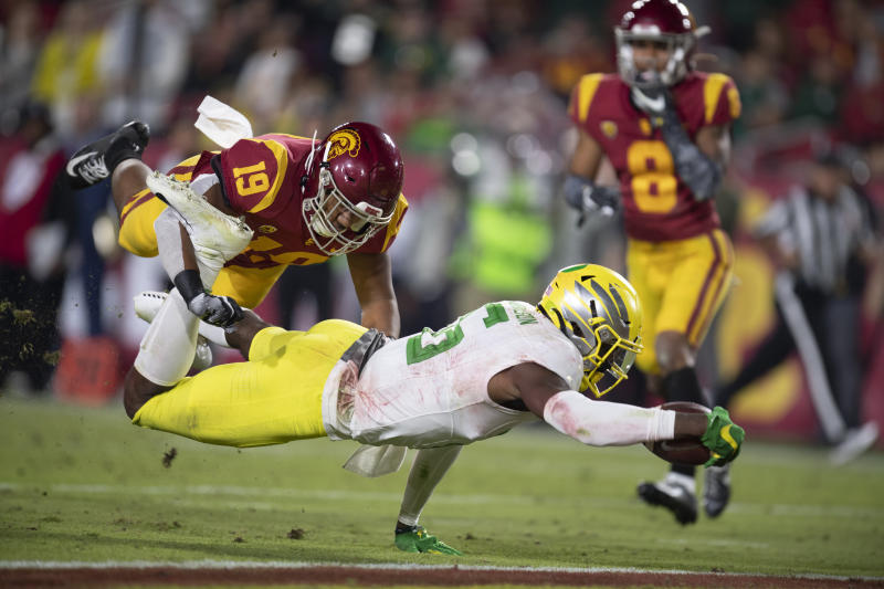 Oregon wide receiver Juwan Johnson, front, dives to score a touchdown past Southern California linebacker Ralen Goforth during the second half of an NCAA college football game Saturday, Nov. 2, 2019, in Los Angeles. (AP Photo/Kyusung Gong)