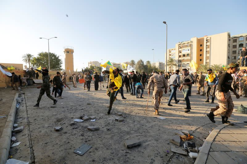 Protesters and militia fighters throw stones towards the U.S. Embassy during a protest to condemn air strikes on bases belonging to Hashd al-Shaabi (paramilitary forces), in Baghdad