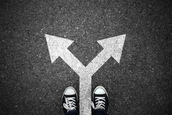 Two shoes in front of an arrow splitting into two directions drawn on the pavement, seen from above