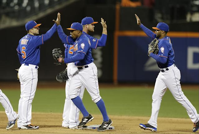 New York Mets' David Wright (5) and Curtis Granderson (3) celebrate with teammates after a baseball game against the St. Louis Cardinals, Wednesday, April 23, 2014, in New York. The Mets won the game 3-2. (AP Photo/Frank Franklin II)