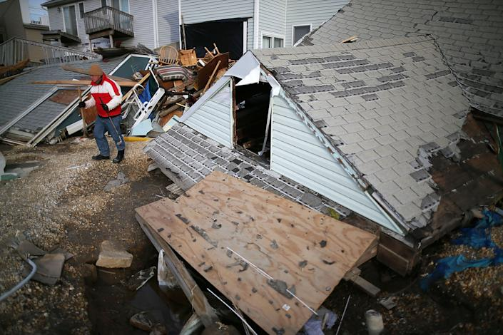 David Mccue stands near the roof to his beach house that was completely demolished by Superstorm Sandy on November 25, 2012 in Ortley Beach, New Jersey. New Jersey Gov. Christie estimated that Superstorm Sandy cost New Jersey $29.4 billion in damage and economic losses. (Photo by Mark Wilson/Getty Images)