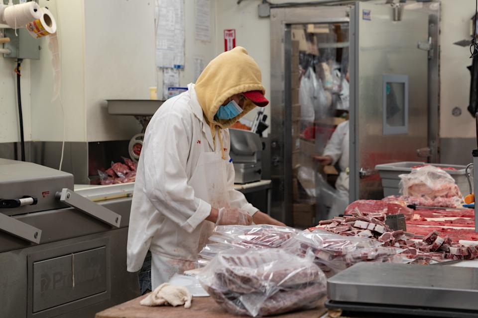 A butcher processes some meat at Vincents Meat Market on April 17, 2020, in Bronx borough of New York City.  Some of the country's largest meat processing plants closed due to the COVID-19 outbreak after a factory in South Dakota was closed after nearly 300 of its 3,700 employees tested positive. (Photo by David Dee Delgado/Getty Images)
