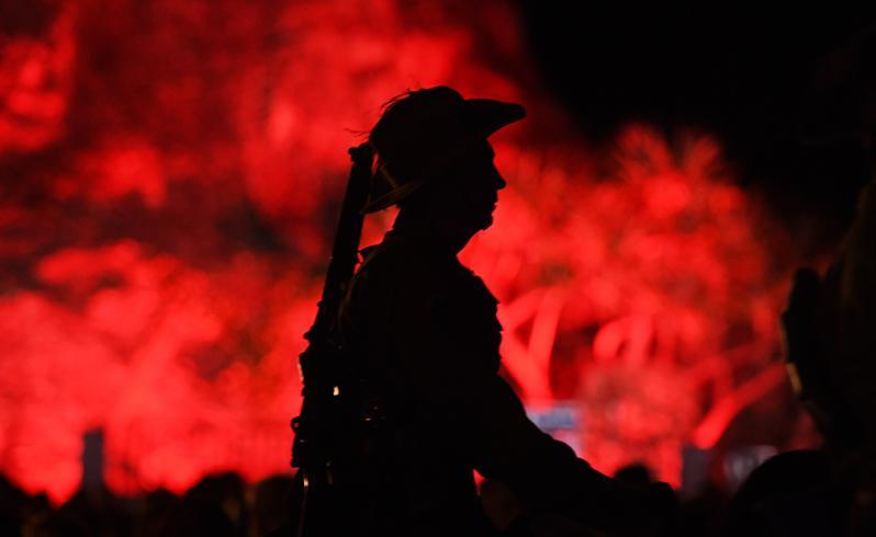 A horseman stands mounted before a red-lit Elephant Rock at Currubin RSL on the Gold Coast. Source: AAP