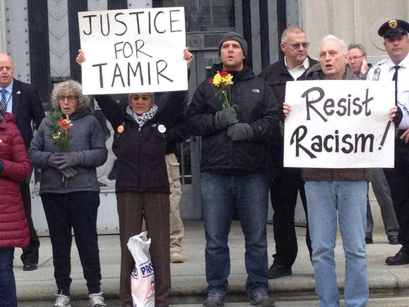 """In this 2016 photo, Martin Gugino, right, holds a sign reading """"Resist Racism,"""" in Washington, D.C."""
