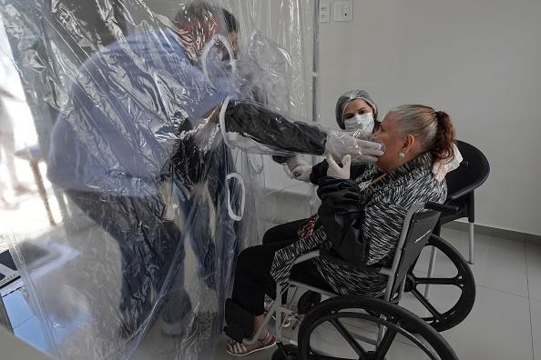 Ossimar Silva (L) touches his 85-year-old mother Carmelita Valverde's face, through a transparent plastic curtain at a senior nursing home in Sao Paulo, Brazil.