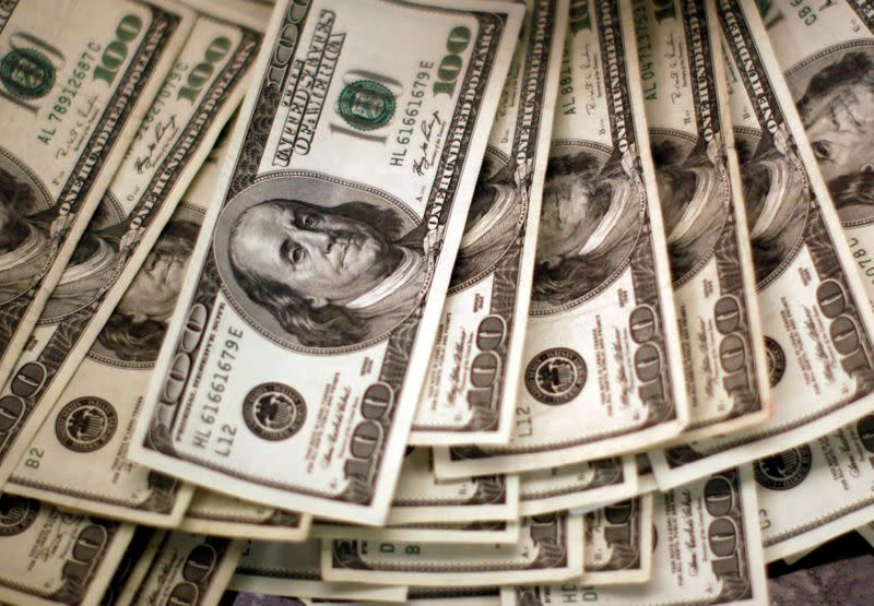 FILE PHOTO: U.S. dollars are counted out by a banker at a bank in Westminster