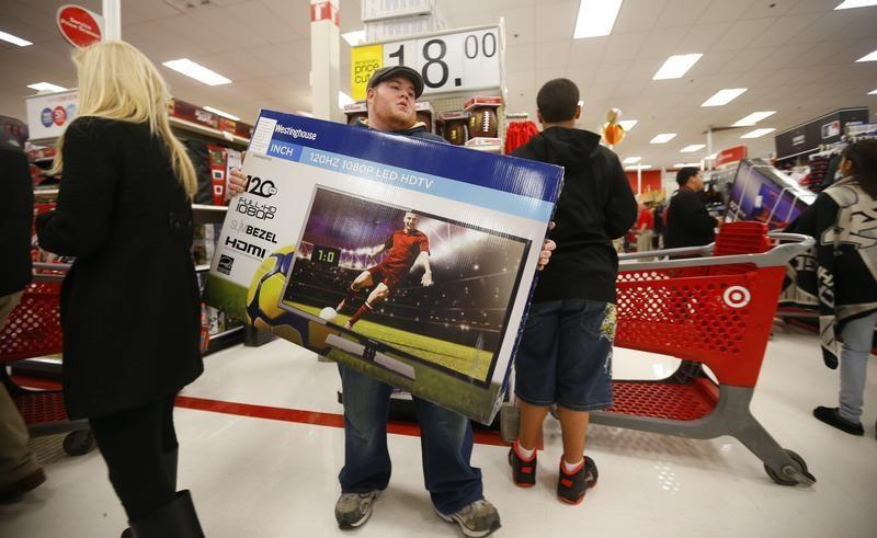 Thanksgiving Day holiday shopper carries a discounted television to the checkout at the Target retail store in Chicago