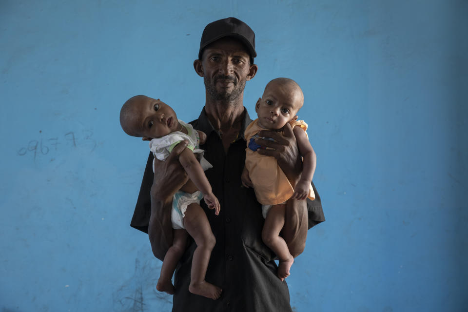 Tigrayan refugee Abraha Kinfe Gebremariam, 40, holds his 4-month-old twin daughters Aden, left, and Turfu, inside their family's shelter in Hamdayet, eastern Sudan, near the border with Ethiopia, on March 23, 2021. Abraha searches their faces for traces of their mother. Babies change, especially this young, he says. But for now, his family agrees, one of the girls does look like Letay. (AP Photo/Nariman El-Mofty)