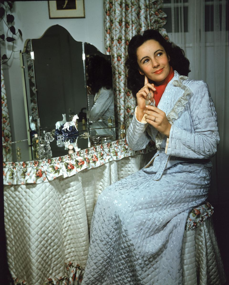 Taylor sits at a mirror-topped vanity table and applies perfume, circa 1940s.