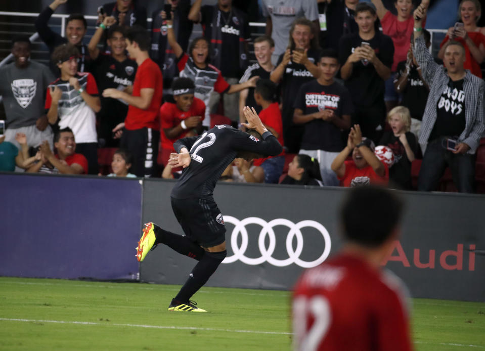 D.C. United midfielder Yamil Asad (22) celebrates his goal past Vancouver Whitecaps goalkeeper Brian Rowe (12) during the first half of an MLS soccer match at Audi Field, Saturday, July 14, 2018, in Washington. (AP Photo/Alex Brandon)