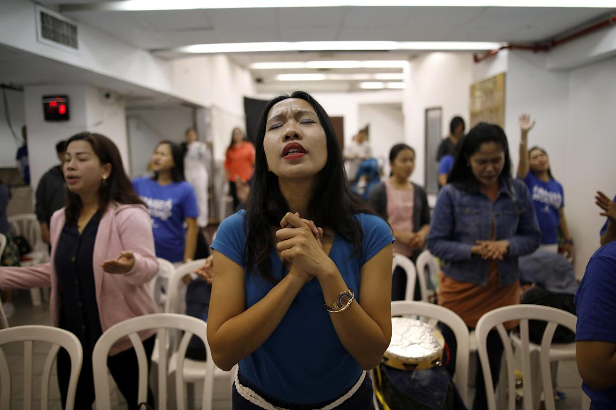 Merry Christ Palacios, a caregiver from the Philippines, during a church service held at the Central Bus Station on April 13. Palacios shops at the station and worships in its church. (Photo: Corinna Kern/Reuters)