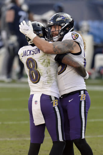 Baltimore Ravens quarterback Lamar Jackson (8) hugs tight end Eric Tomlinson after the Ravens beat the Tennessee Titans in an NFL wild-card playoff football game Sunday, Jan. 10, 2021, in Nashville, Tenn. (AP Photo/Mark Zaleski)