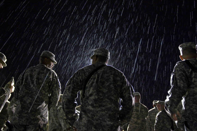 <p>1st Lt. Nikesh Kapadia, 24, center, of Queens, N.Y., with the U.S. Army's 4th Brigade Combat Team, 101st Airborne Division out of Fort Campbell, Ky., stands in the rain while waiting to go through customs at the Transit Center in Manas, Kyrgyzstan, on the way home after completing a deployment in Afghanistan on Aug. 10, 2011. The 4th Brigade Combat Team, 101st Airborne Division is returning home after a year in Afghanistan as the last brigade to deploy as part of President Obama's 30,000 troop surge. (AP Photo/David Goldman) </p>