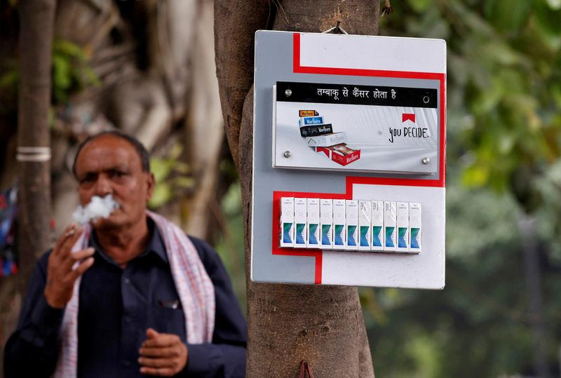 FILE PHOTO: A man smokes next to a cigarette advertisement hung on a tree at a marketplace in New Delhi