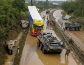German army soldiers work on flooded cars and a truck on a road in Erftstadt, Germany, Saturday, July 17, 2021. Due to strong rain falls the small Erft river went over the banks causing massive damages. (AP Photo/Michael Probst)