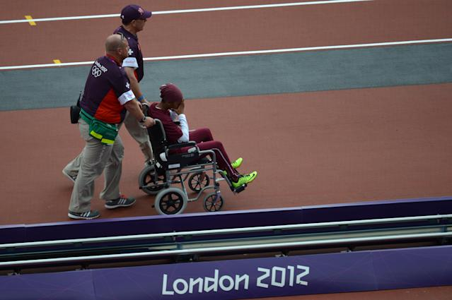 Qatar's Noor Hussain Al-Malki leaves the field on a wheelchair after suffering an injury in the women's 100m heats at the athletics event during the London 2012 Olympic Games on August 3, 2012 in London. AFP PHOTO / JEWEL SAMADJEWEL SAMAD/AFP/GettyImages