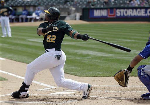 Oakland Athletics' Yoenis Cespedes, left, singles against the Kansas City Royals during the second inning of a baseball game on Wednesday, April 11, 2012, in Oakland, Calif. (AP Photo/Marcio Jose Sanchez)