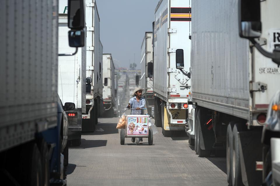 A street vendor sells ice cream to cargo trucks drivers lining up to cross to the United States at Otay commercial crossing port in Tijuana, Baja California state, on June 6, 2019, Mexico. - The US warned Mexico Thursday it needed to make more concessions on slowing migration to avoid President Donald Trump's threatened tariffs, as the Mexican leader announced he would visit the border to