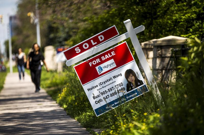 "A woman walks towards a ""for sale"" sign of a home that has been sold in Toronto. (REUTERS/Mark Blinch)"