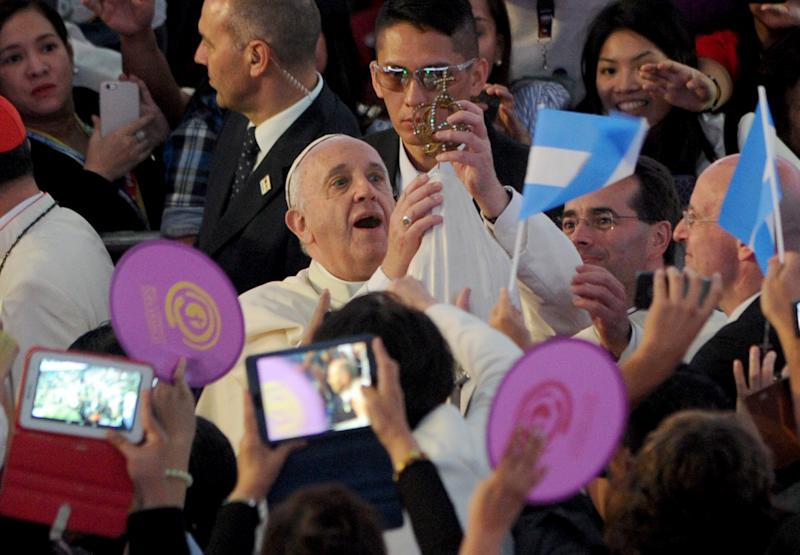 Pope Francis holds a religious icon as he arrives to meet Filipino families at the Mall of Asia Arena in Manila on January 16, 2015 (AFP Photo/Jay Directo)