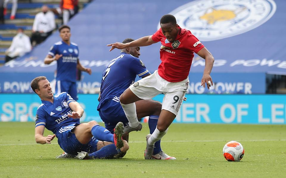 Manchester United's Anthony Martial (right) is brought down by a challenge by Leicester City's Jonny Evans (left) and Wes Morgan.
