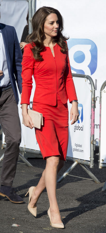 <p>In a bright red, figure-flattering Armani skirt suit, beige clutch and beige Rupert Sanderson pumps at the opening of The Global Academy in partnership with the Heads Together charity.</p>