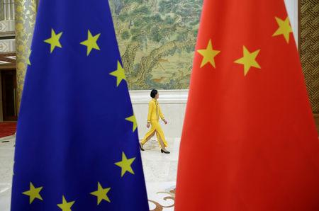 An attendant walks past EU and China flags ahead of the EU-China High-level Economic Dialogue in Beijing