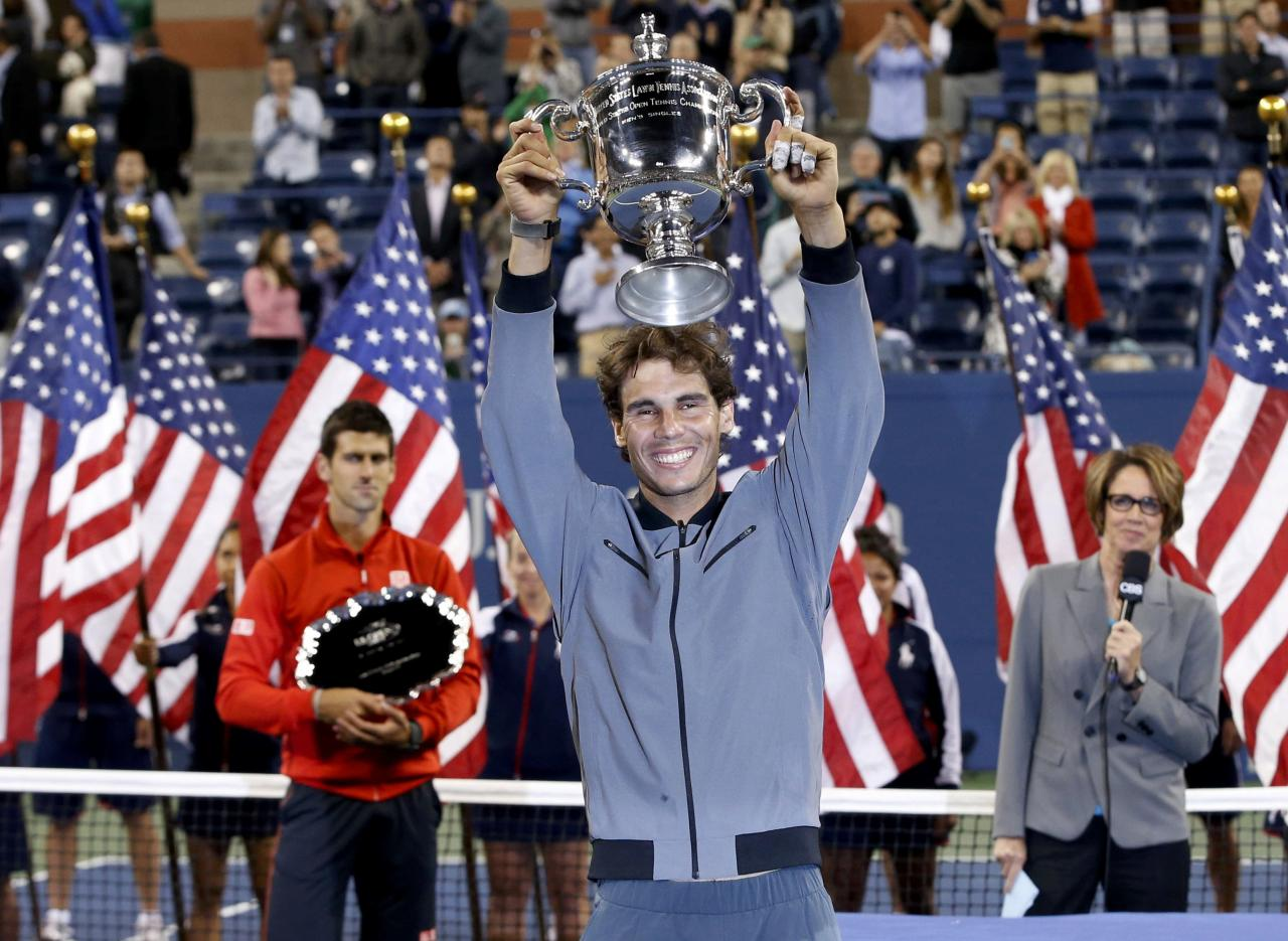 Rafael Nadal of Spain raises his trophy after defeating Novak Djokovic of Serbia (L) in their men's final match at the U.S. Open tennis championships in New York, September 9, 2013. REUTERS/Mike Segar (UNITED STATES - Tags: SPORT TENNIS TPX IMAGES OF THE DAY)