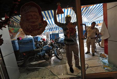 An employee pulls down the shutter of a Dominos Pizza outlet near a policeman after it was ransacked by activists in a Mumbai suburb