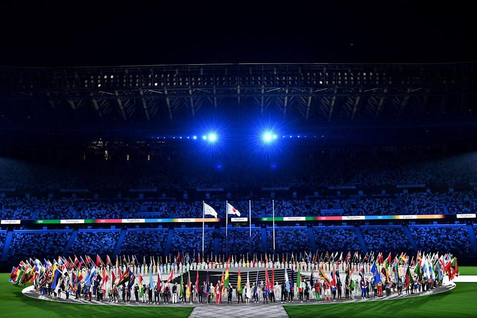 <p>Athletes delegations pose with their national flag during the closing ceremony of the 2020/2021 Tokyo Olympic Games.</p>