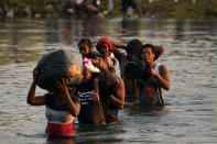 Migrants, many from Haiti, wade across the Rio Grande from Del Rio, Texas, to return to Ciudad Acuna, Mexico, Tuesday, Sept. 21, 2021, to avoid deportation from the U.S. The U.S. is flying Haitians camped in a Texas border town back to their homeland and blocking others from crossing the border from Mexico. (AP Photo/Fernando Llano)