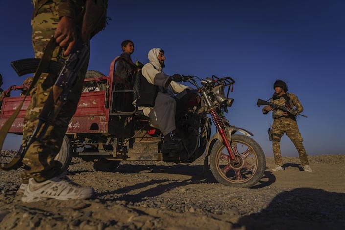 Afghan police officers in sneakers and camouflage talk to two people on a three-wheel vehicle.