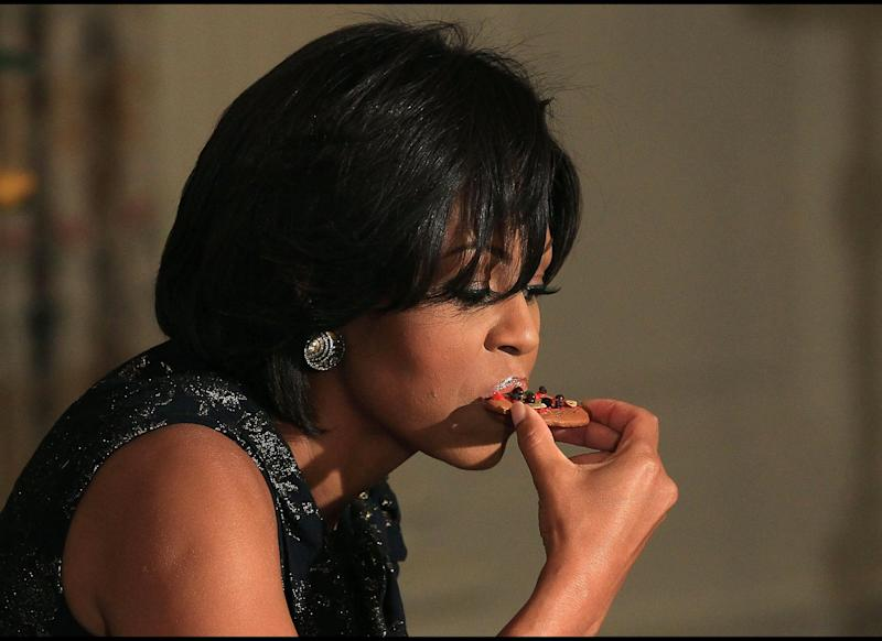 WASHINGTON, DC - DECEMBER 01: First lady Michelle Obama takes a bite of a cookie she made while participating in an event at the White House on December 1, 2010 in Washington, DC. The first lady hosted the event to honor the military families who organize the Quantico and Anacostia branches of the Marine Corps Reserve annual Toys for Tots drive. (Photo by Mark Wilson/Getty Images)